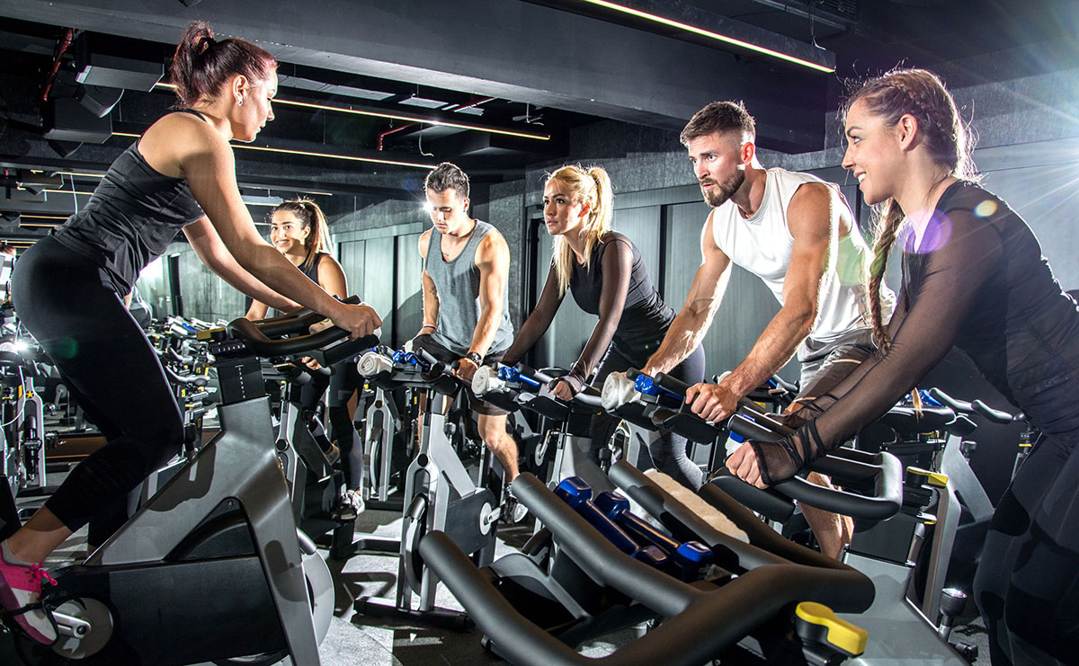 men and women on indoor fitness bikes in a class setting