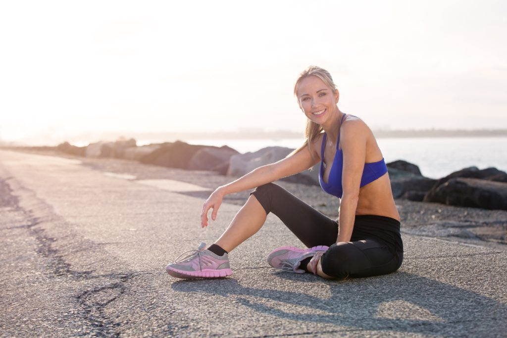 fit blonde woman wearing an attractive outfit sitting on the ground outside on the asphalt near some rocks and water with the sunshine in the background smiling because she includes balance training in her workout routine.