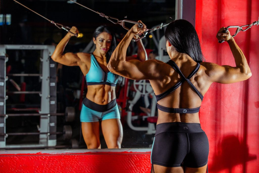 hot women working out in her home gym with the best workout machines for home.